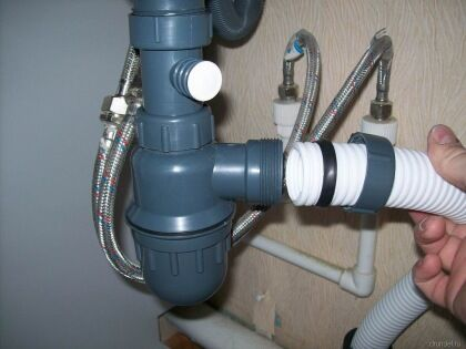 Подсоединяем к выходному отверстию сифона отводящий патрубок и крепим его к установочной манжете в канализационной трубе.