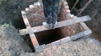 Процесс кладки стен квадратной выгребной ямы