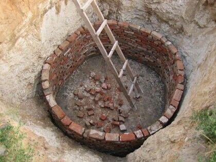 Процесс кладки стен круглой выгребной ямы