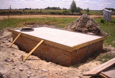 Укладка плиты перекрытия на выгребную яму