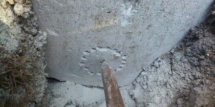 По центру устанавливаем лом и ударяем им по бетонному кольцу