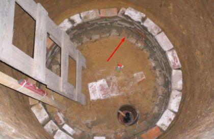 Основание под стенками будущей выгребной ямы указано стрелкой. В центре можно увидеть несколько уложенных кирпичей – они необходимы для разбития струи канализационных стоков и равномерного их распределения по дну сооружения