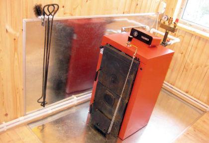 Пример установки твердотопливного котла. Отметьте для себя расположение устройства – между ним и стенами есть большие зазоры. Также можно заметить экраны из негорючего материала на полу и на одной из стен