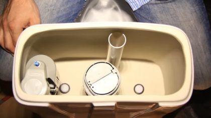 Собранный и смонтированный сливной бачок изнутри. Можно увидеть головки болтов, сливной и заливной клапаны, поплавок, а также переливную трубу