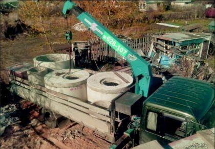 Доставка и разгрузка бетонных изделий с помощью грузовика с краном-манипулятором. Можно увидеть устройство круглых плит с отверстиями, которые будут использованы в качестве крышек резервуаров ЛОС