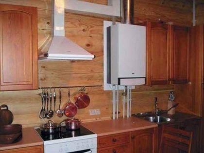 Газовый котел на кухне. Обратите внимание на подложку из негорючего материала на стене за ним