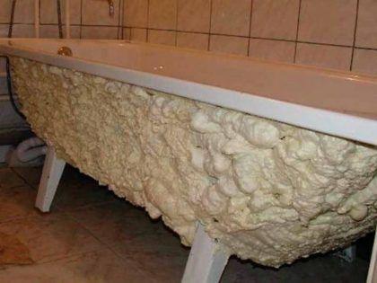 Использование монтажной пены для утепления и шумовоизоляции ванны из стали. Нанесенный слой впоследствии будет закрыт декоративной стенкой